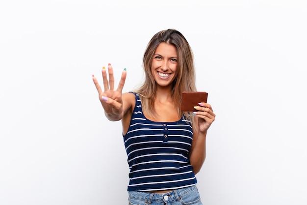 Junge hübsche frau lächelt und sieht freundlich aus, zeigt nummer vier oder viertens mit der hand nach vorne und zählt mit einer lederbrieftasche herunter.