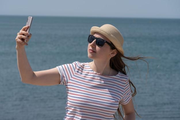 Junge hübsche frau macht ein foto von sich am telefon vor dem hintergrund des blauen seehafens...