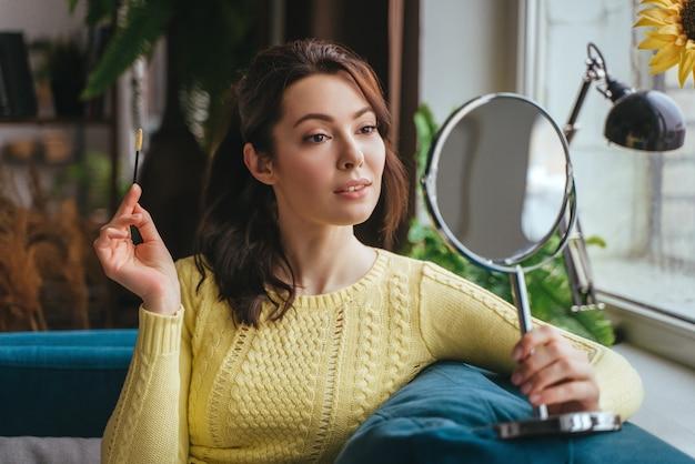 Junge hübsche frau macht make-up zu hause, während sie in den spiegel schaut Premium Fotos