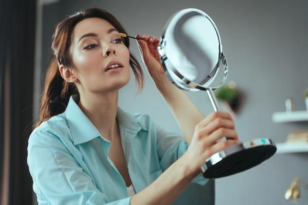 Junge hübsche frau macht make-up zu hause, während sie in den spiegel schaut