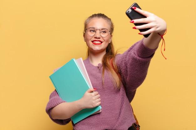 Junge hübsche frau macht selfie-foto mit smartphone, während sie bücher hält