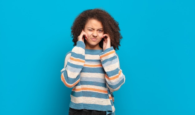 Junge hübsche frau mit afro-haar und gestreiftem pullover, der auf blauer wand aufwirft