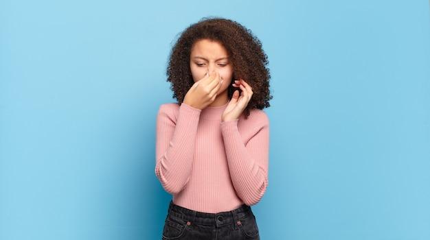 Junge hübsche frau mit afro-haar und rosa pullover, der auf blauer wand aufwirft