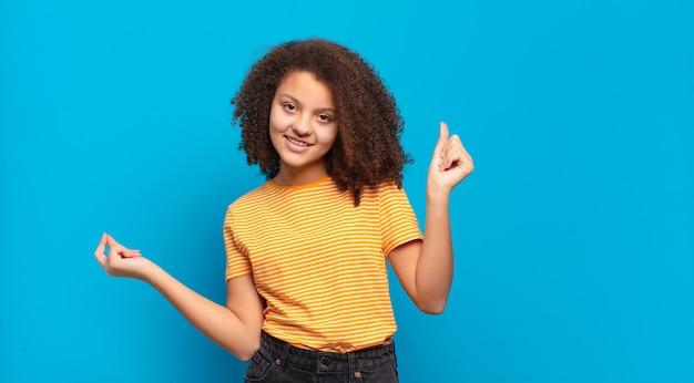 Junge hübsche frau mit afro-haaren und gelbem hemd, das auf blauer wand aufwirft