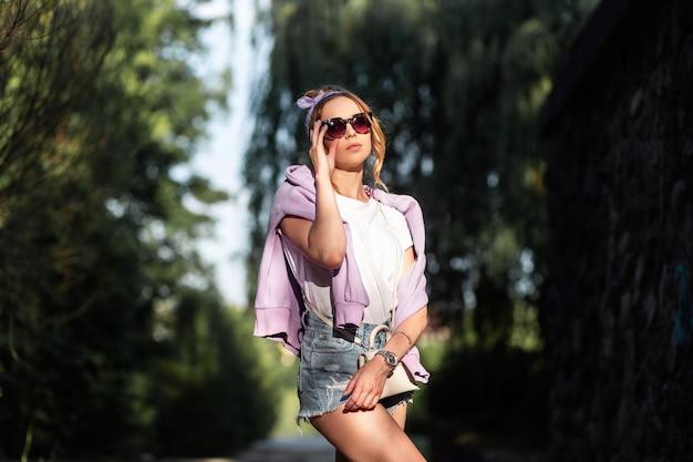 Junge hübsche frau mit bandana in modischer jeanskleidung richtet sonnenbrillen auf und geht im freien