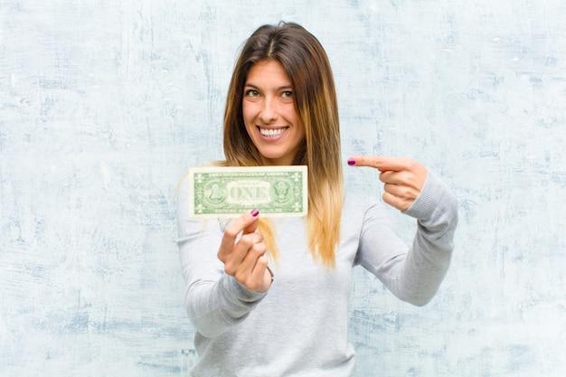 Junge hübsche frau mit banknotenschmutzwand