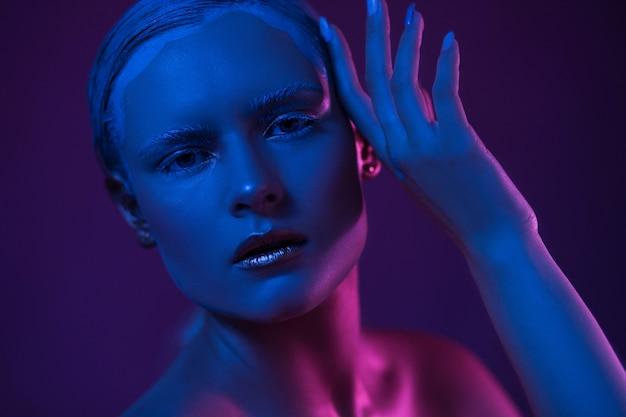 Junge hübsche frau mit coolem make-up. neonblaue und lila lichter im gesicht.