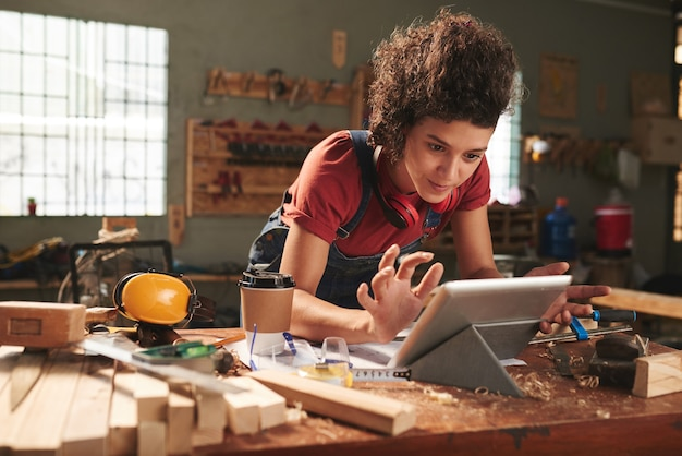 Junge hübsche frau mit dem lockigen haar, das tutorial der holzbearbeitung auf digitalem tablett beobachtet, während sie sich auf unordentlichen tisch stützt, der mit sägemehl bedeckt wird