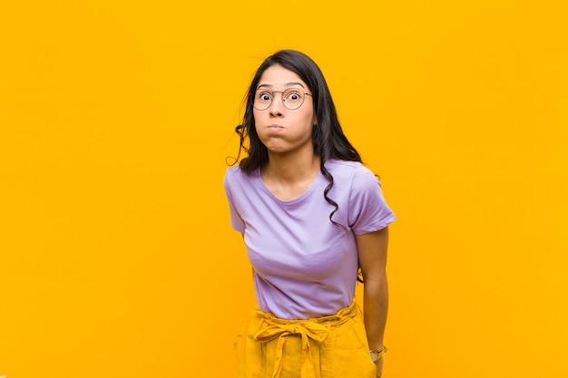 Junge hübsche frau mit einem albernen, verrückten, überraschten ausdruck, pochenden wangen, fühlte sich gestopft, fett und voller essen gegen orangefarbene wand