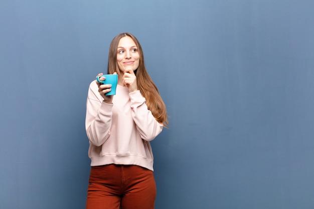 Junge hübsche frau mit einem kaffee gegen blaue wand mit einem kopienraum