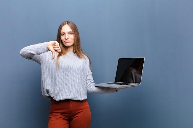 Junge hübsche frau mit einem laptop gegen blaue wand mit einem kopienraum