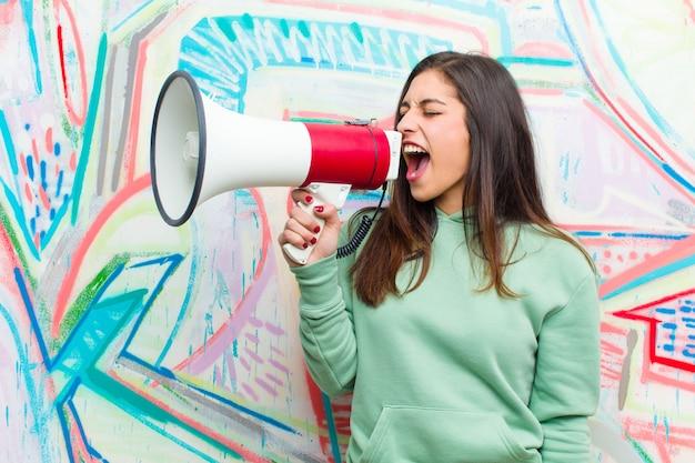 Junge hübsche frau mit einem megaphon gegen graffitiwand