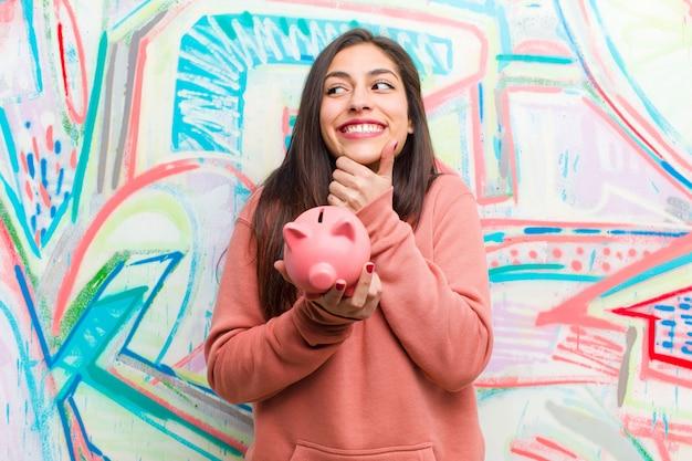 Junge hübsche frau mit einem sparschwein gegen graffitiwand