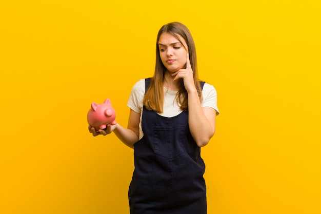 Junge hübsche frau mit einem sparschwein gegen orange hintergrund