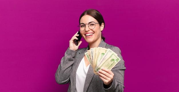 Junge hübsche frau mit einem telefon und dollarbanknoten. geschäftskonzept