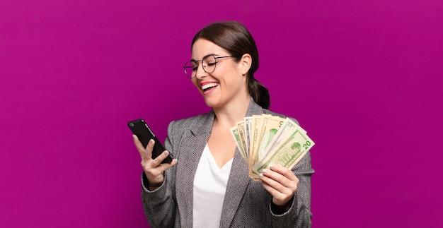 Junge hübsche frau mit einem telefon und dollarbanknoten. unternehmenskonzept
