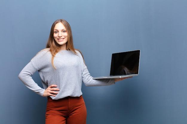 Junge hübsche frau mit einer blauen wand des laptops mit einem copyspace