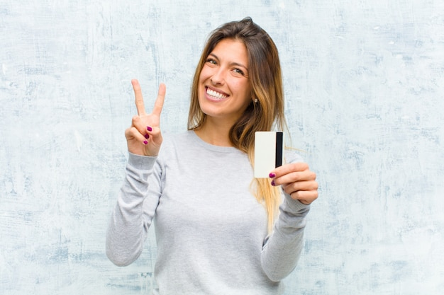 Junge hübsche frau mit einer kreditkarte grunge wand