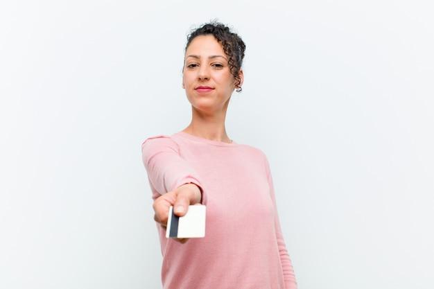 Junge hübsche frau mit einer kreditkartenweißwand