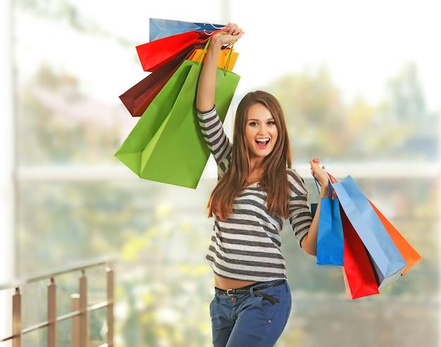 Junge hübsche frau mit einkaufspaketen im geschäft