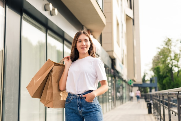 Junge hübsche frau mit einkaufstüten, die auf der stadtstraße gehen