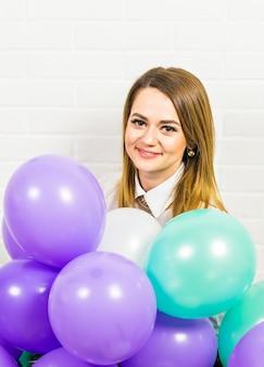 Junge hübsche frau mit farbigen luftballons