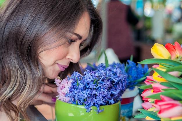 Junge hübsche frau mit frühlingsblumen bouquet. frau riechender blumenstrauß der hyazinthe. mädchen mit der hyazinthe