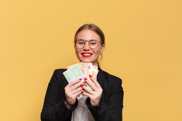Junge hübsche frau mit glücklichem und überraschtem ausdruck, der geld hält