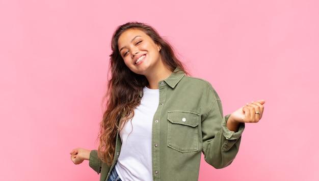 Junge hübsche frau mit grünem jeanshemd posiert auf rosa wand