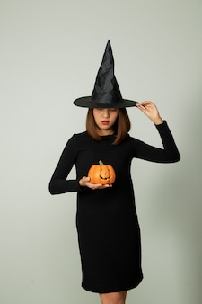 Junge hübsche frau mit hexenhut, die halloween kürbis jack o laterne dekor hält