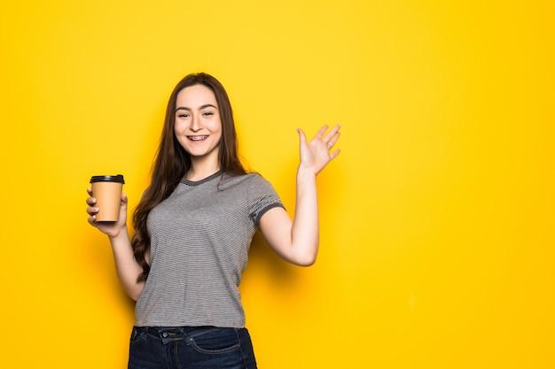 Junge hübsche frau mit kaffeetasse, die mit händen auf gelber wand winkt