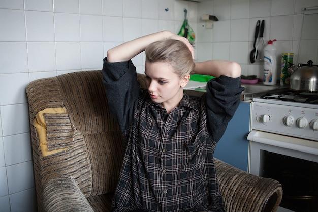 Junge hübsche frau mit kurzen haaren, die in der alten vintage-küche im sessel sitzt