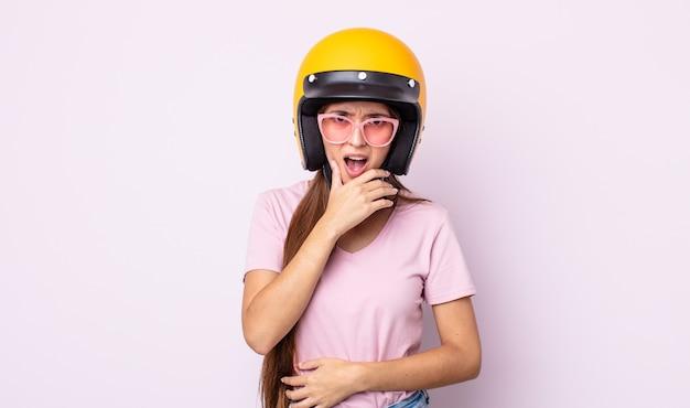 Junge hübsche frau mit mund und augen weit offen und hand am kinn. motorradfahrer und helm