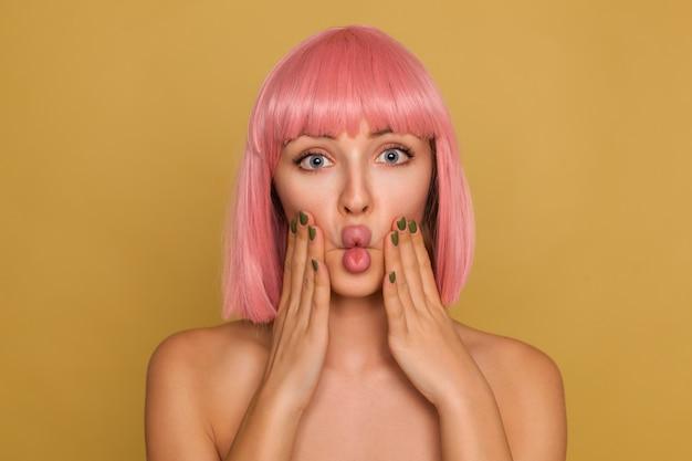 Junge hübsche frau mit offenen augen mit rosa bob-frisur, die erhobene hände auf ihren wangen hält und gesichter macht, während sie über senfwand steht