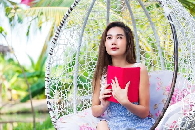 Junge hübsche frau mit rotem tagebuch im park