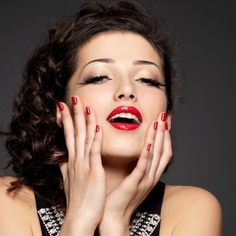 Junge hübsche frau mit roter maniküre und lippen. model mit strahlend positiven emotionen