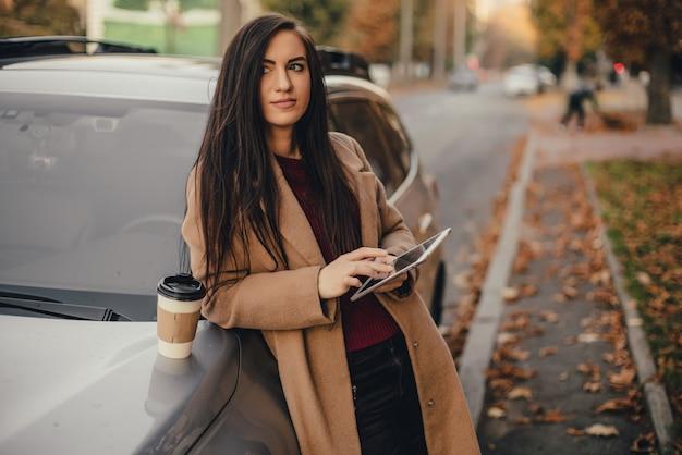 Junge hübsche frau mit tasse kaffee und sms-blog auf tablette im herbstpark nahe fahrzeug