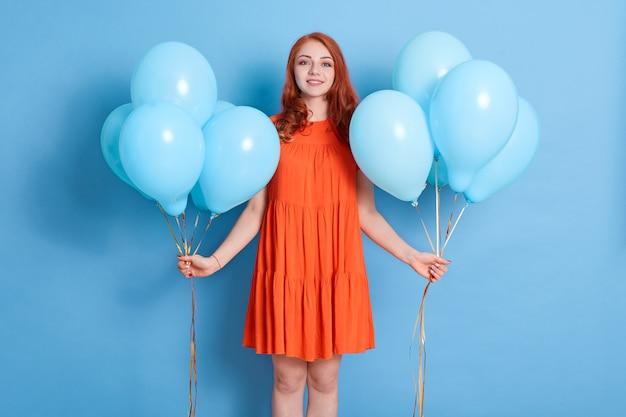 Junge hübsche frau mit zwei luftballons, die gegen blaue wand stehen