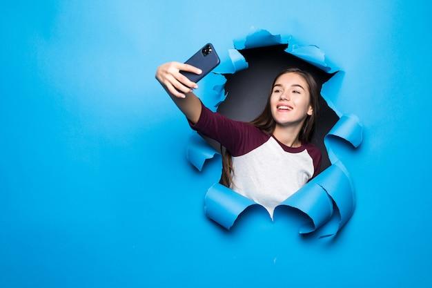Junge hübsche frau nehmen selfie am telefon, während sie durch blaues loch in papierwand schauen.