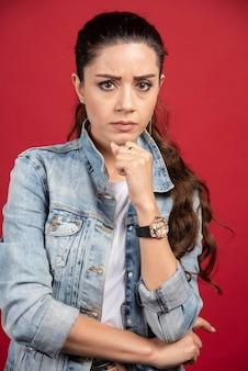 Junge hübsche frau posiert in jeansjacke auf rotem grund. foto in hoher qualität