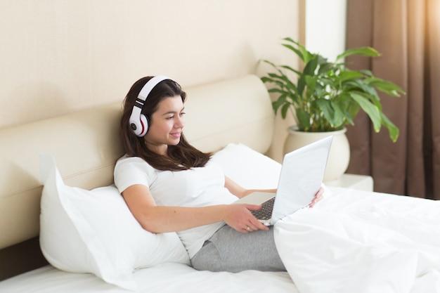 Junge hübsche frau ruht sich mit laptop auf dem bett aus und hört eine musik auf