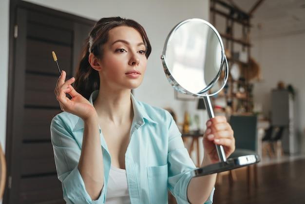 Junge hübsche frau schminkt sich zu hause beim blick in den spiegel