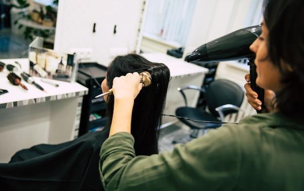 Junge hübsche frau sitzt im sessel in einem schönheitssalon und lässt sich von einem lächelnden professionellen stylisten die haare trocknen.