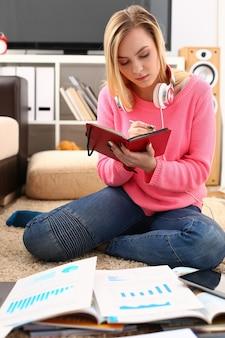 Junge hübsche frau studie im wohnzimmer halten buch in den armen