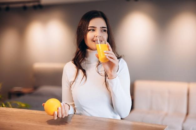 Junge hübsche frau trinkt orangensaft in der küche zu hause.