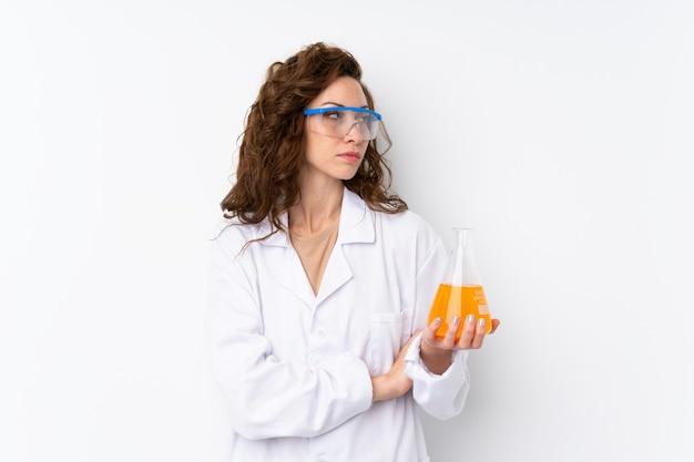 Junge hübsche frau über lokalisierter wand mit einem wissenschaftlichen reagenzglas und schauen seitlich