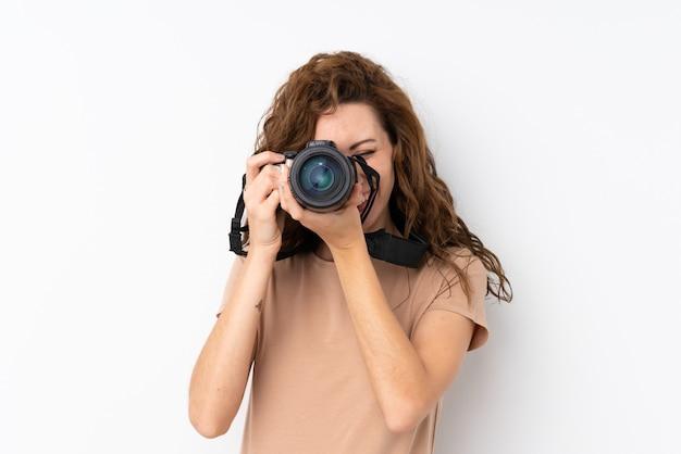 Junge hübsche frau über lokalisierter wand mit einer berufskamera