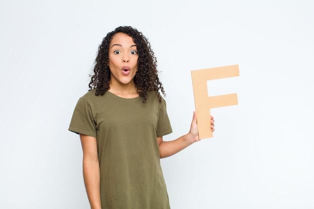 Junge hübsche frau überrascht, schockiert, erstaunt, den buchstaben f des alphabets haltend, um ein wort oder einen satz zu bilden