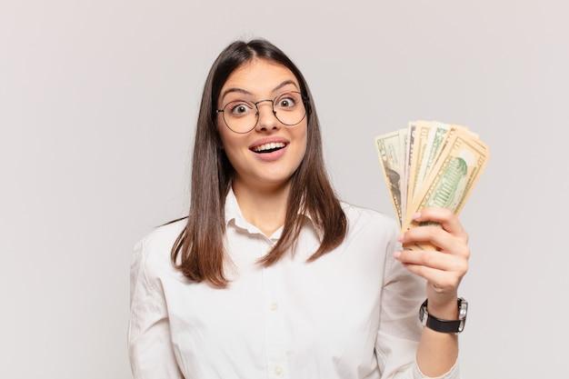 Junge hübsche frau überraschter ausdruck und hält dollarbanknoten