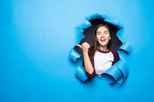 Junge hübsche frau zeigte seite, während sie durch blaues loch in papierwand schaut.